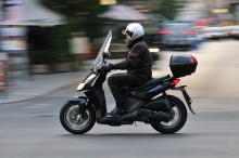 Man ride a scooter in Budapest at main street. (panning camera for blur background)